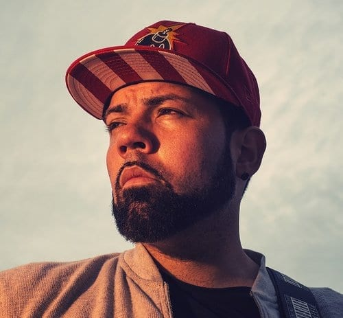 A man with a beard and a red baseball cap