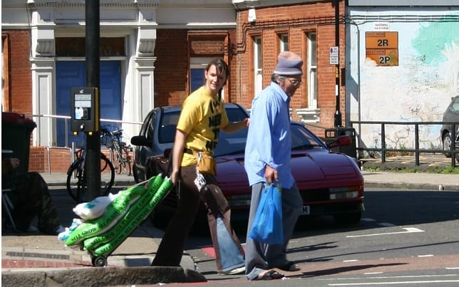 Two people walking across the street. One is holding a blue plastic bag, and the other is dragging sandbags
