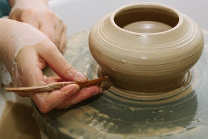 Someone making a pot on a pottery wheel