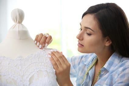 A woman sewing a wedding dress
