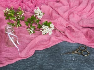 White Hawthorn blossoms on pink fabric with scissors and a jam jar