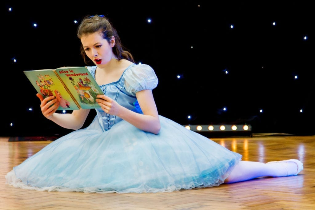 A female actor in a blue dress is reading a book