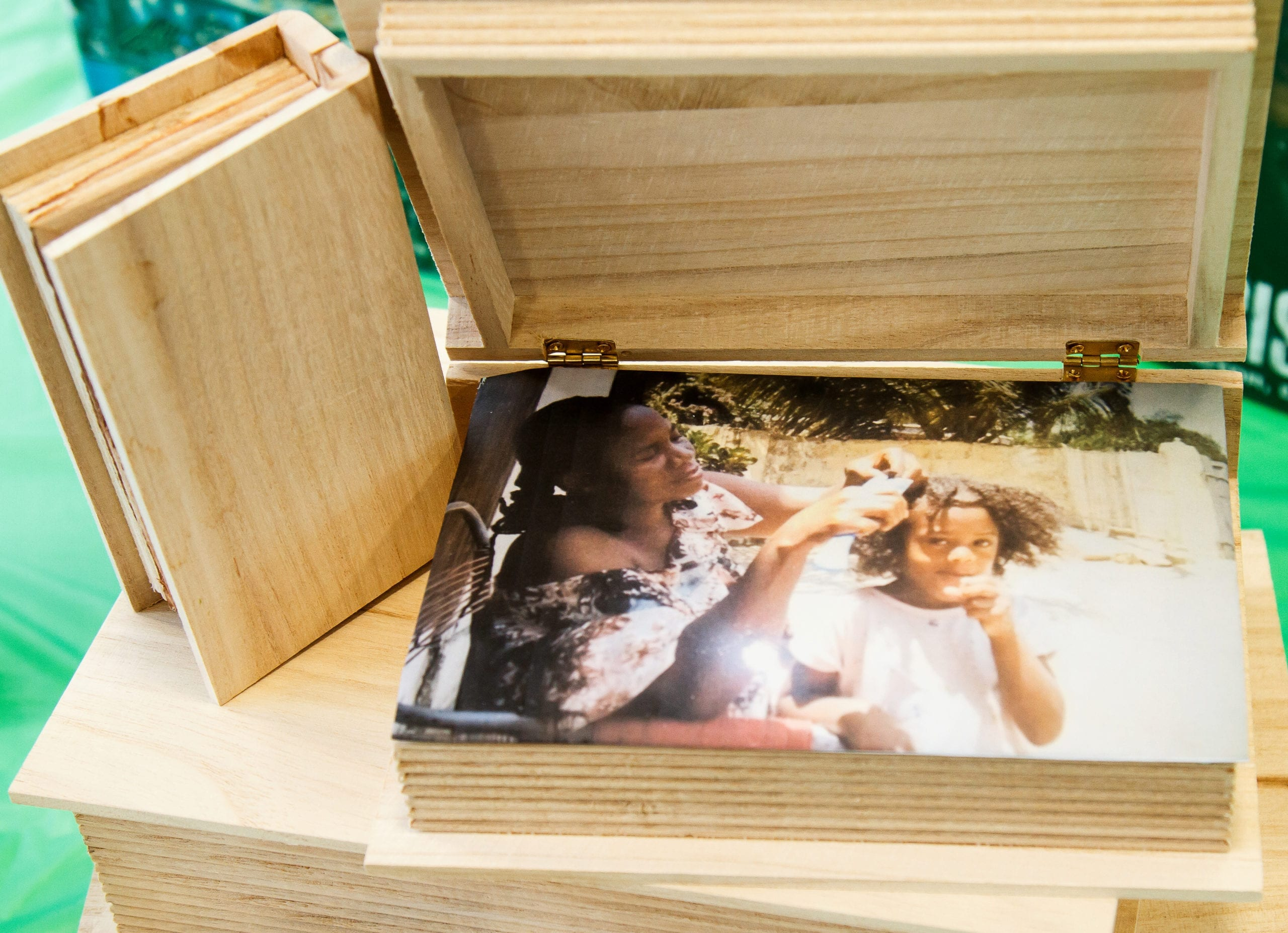 A wooden book with a photo of a woman braiding a young girls hair inside