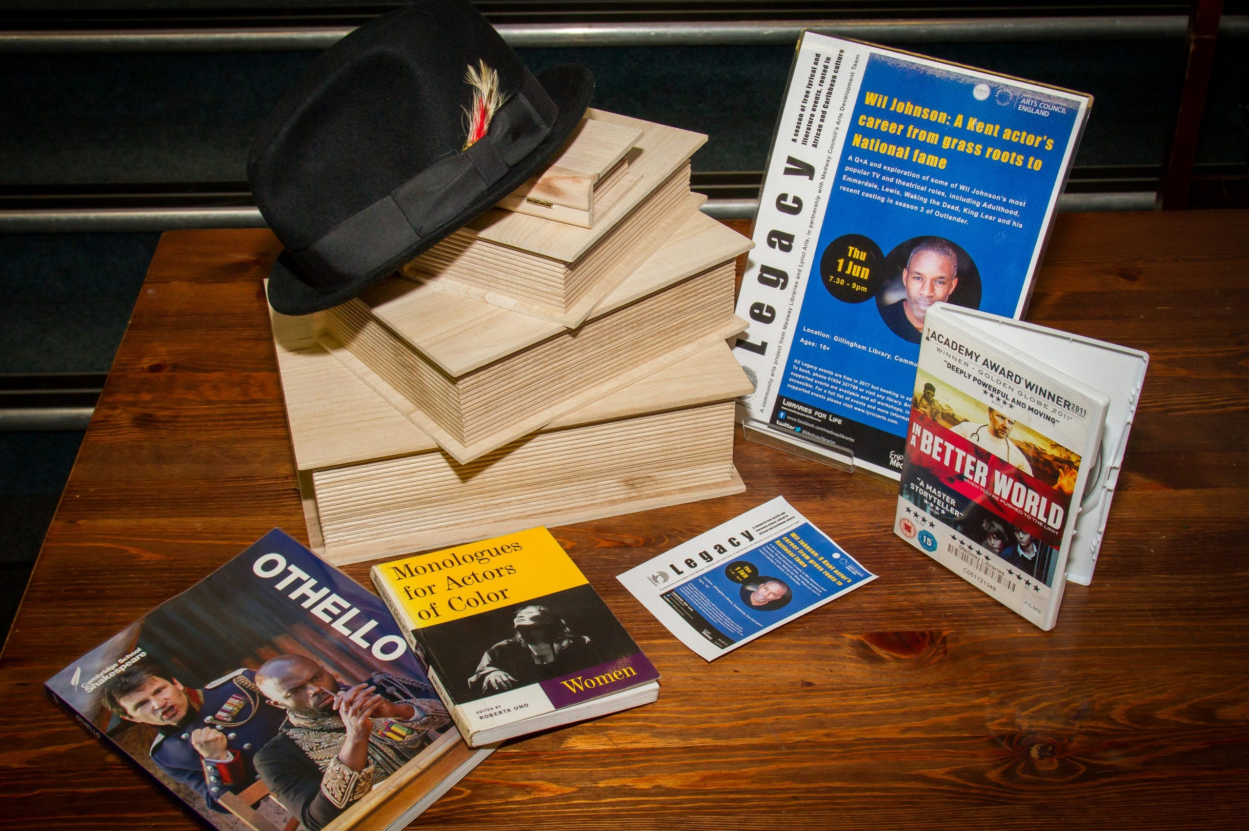 A display with a poster for a Legacy event, a black hat, wooden books and a DVD