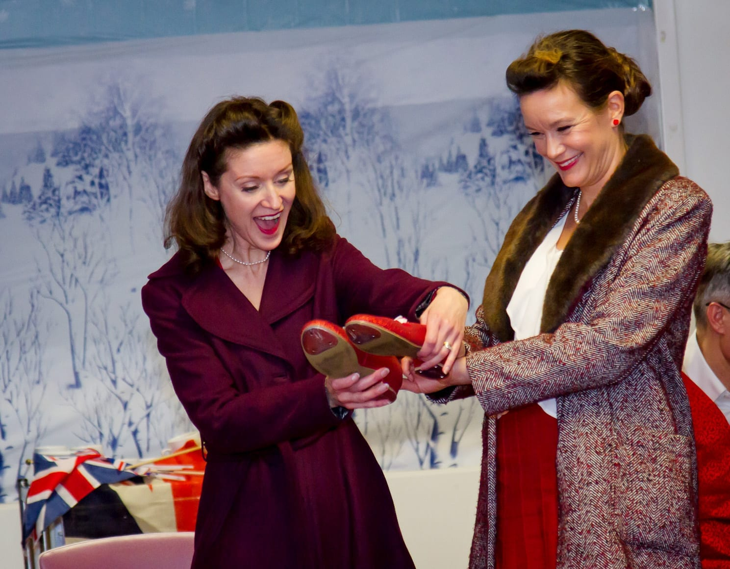 A woman presenting another woman with a pair of red shoes