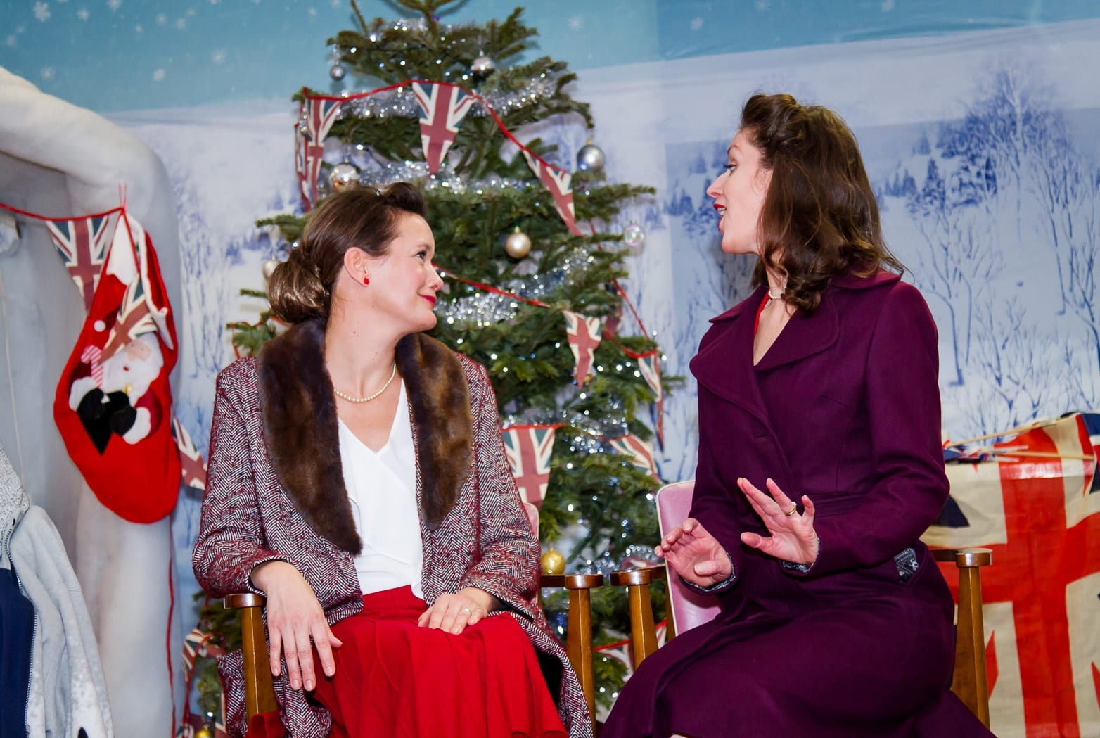 Two women sat in front of a Christmas tree