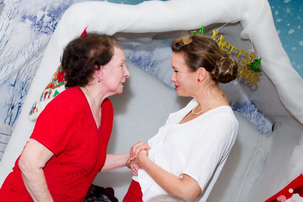 Two women holding hands and looking into each others eyes at a Christmas themed event