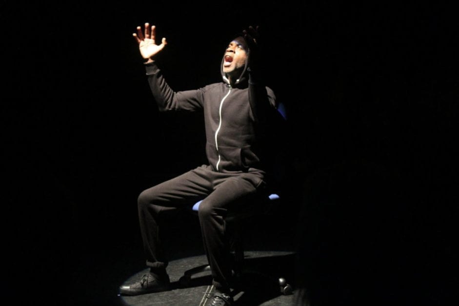 A male actor performs while sitting on a blue chair