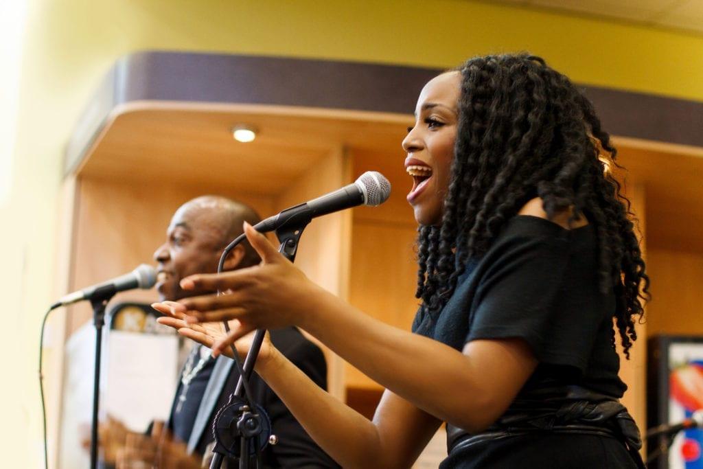 Two singers dressed in black, singing into microphones