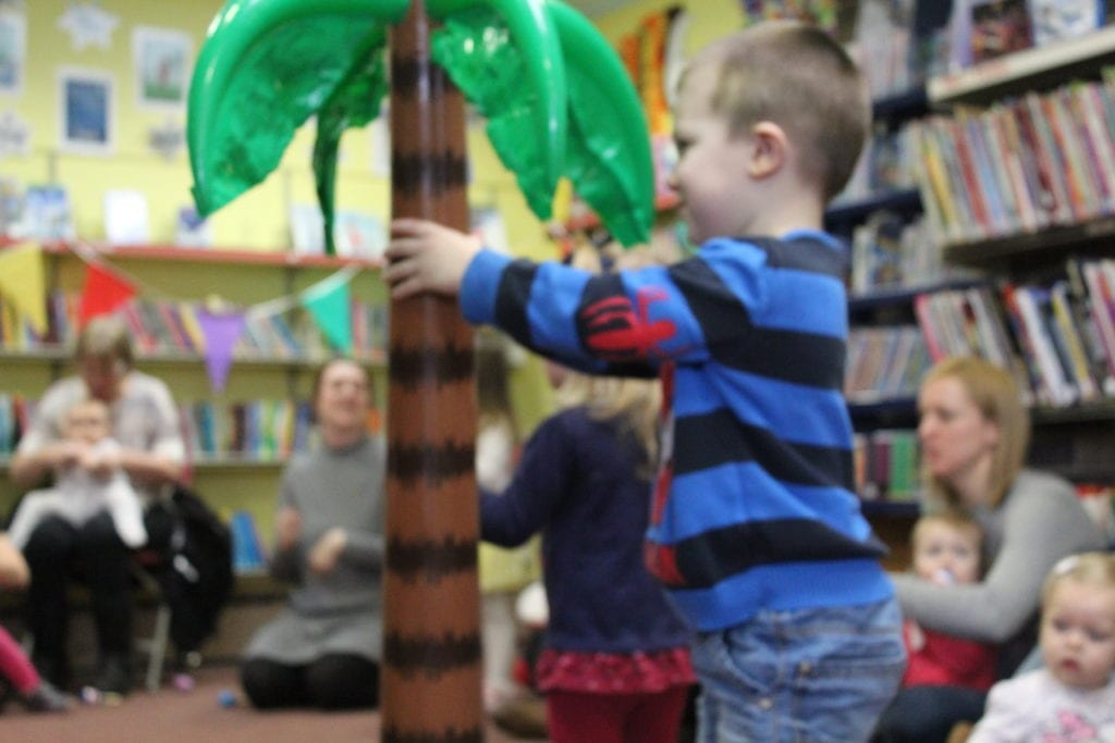 A young boy with a blow up pine tree at an event in a library