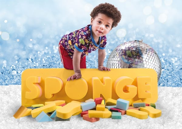 A young boy climbing on a sign reading 'Sponge' with lots of foam sponges in front of it