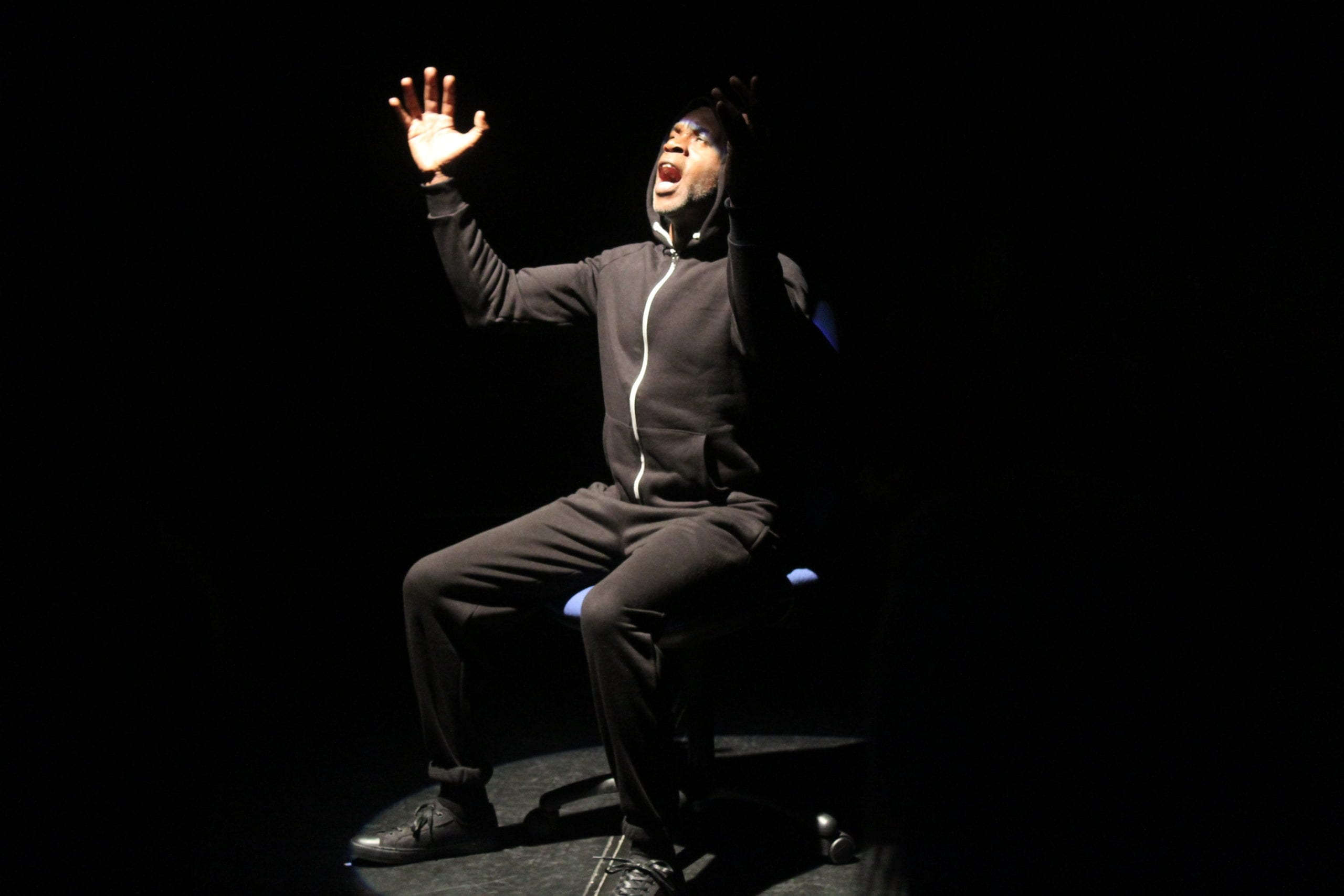 A male actor in a black tracksuit performing