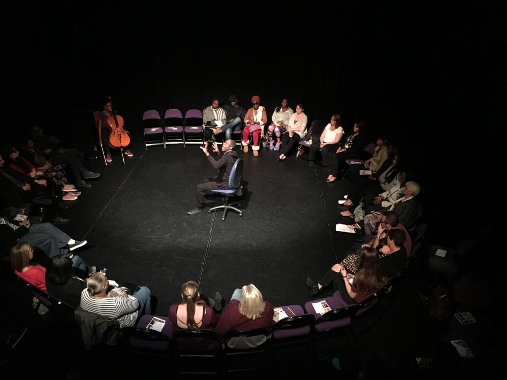 A male actor performs in the middle of a circle of audience members
