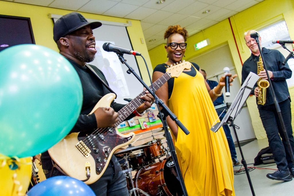 A live band with a singer, electric guitarist, saxophonist and a drummer