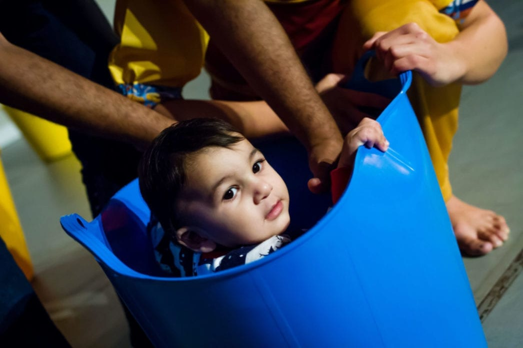 A child in a blue bucket as part of a theatrical performance