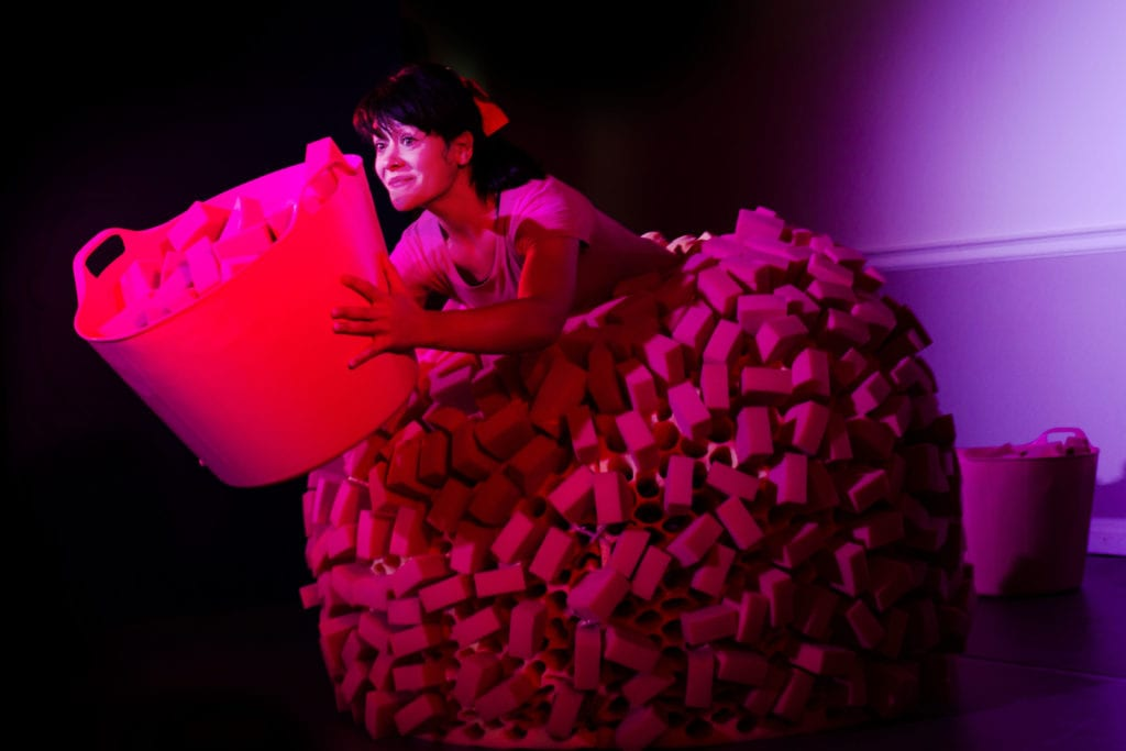 A woman in a skirt made of sponges, holding a bucket of sponges.