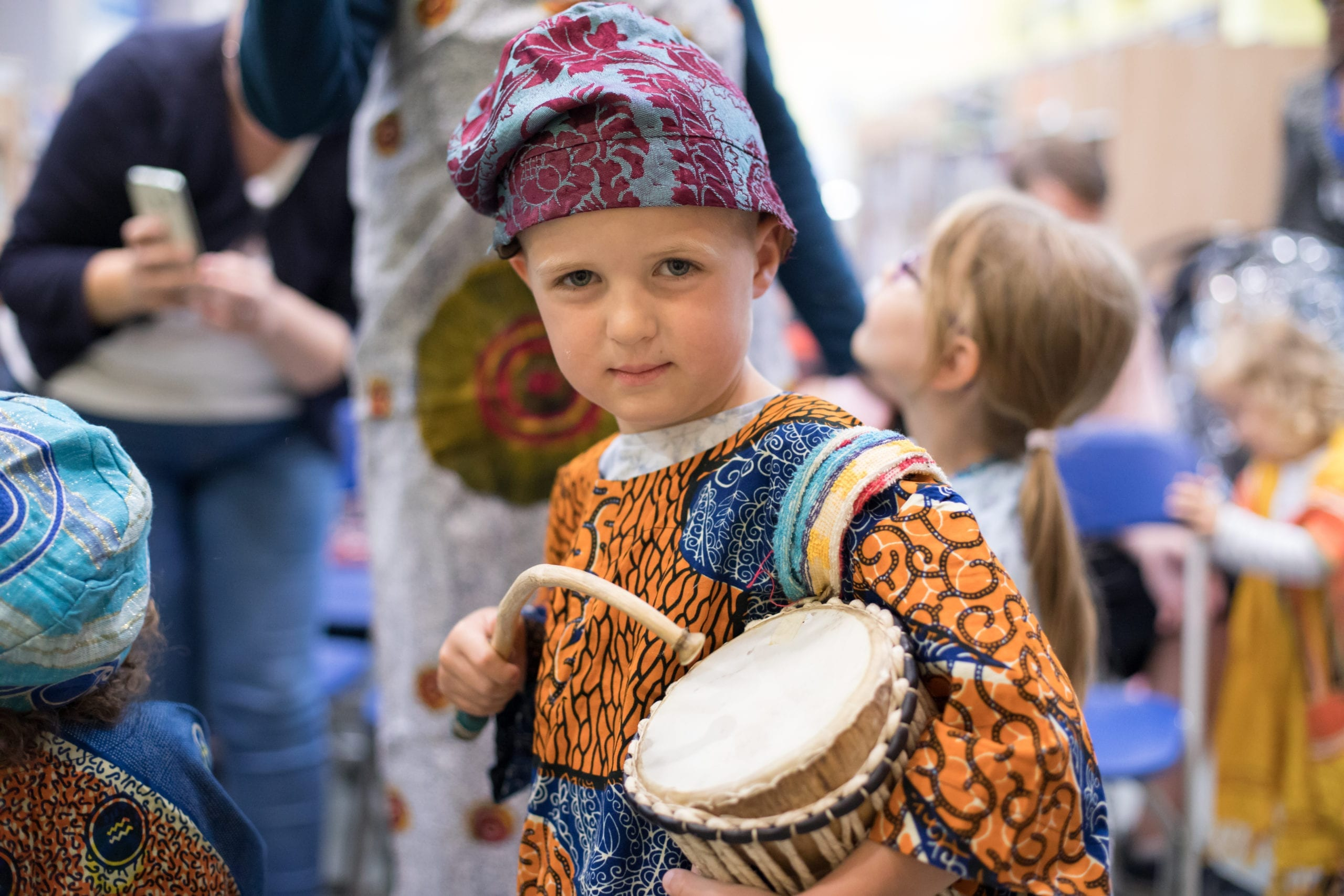 A young child playing a drum