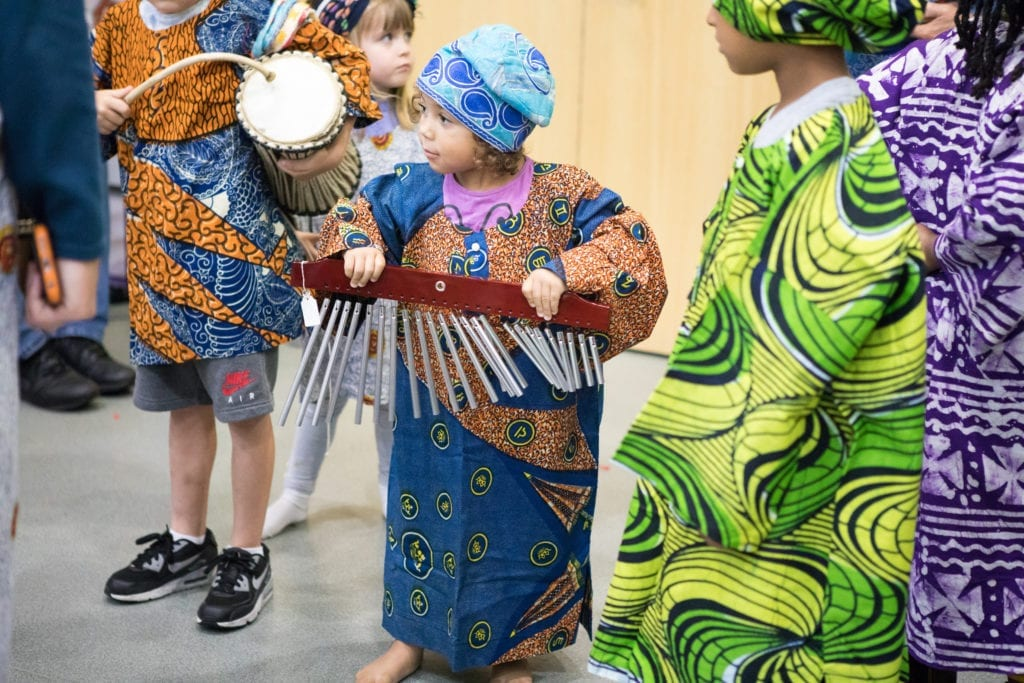 Young children playing percussion instruments