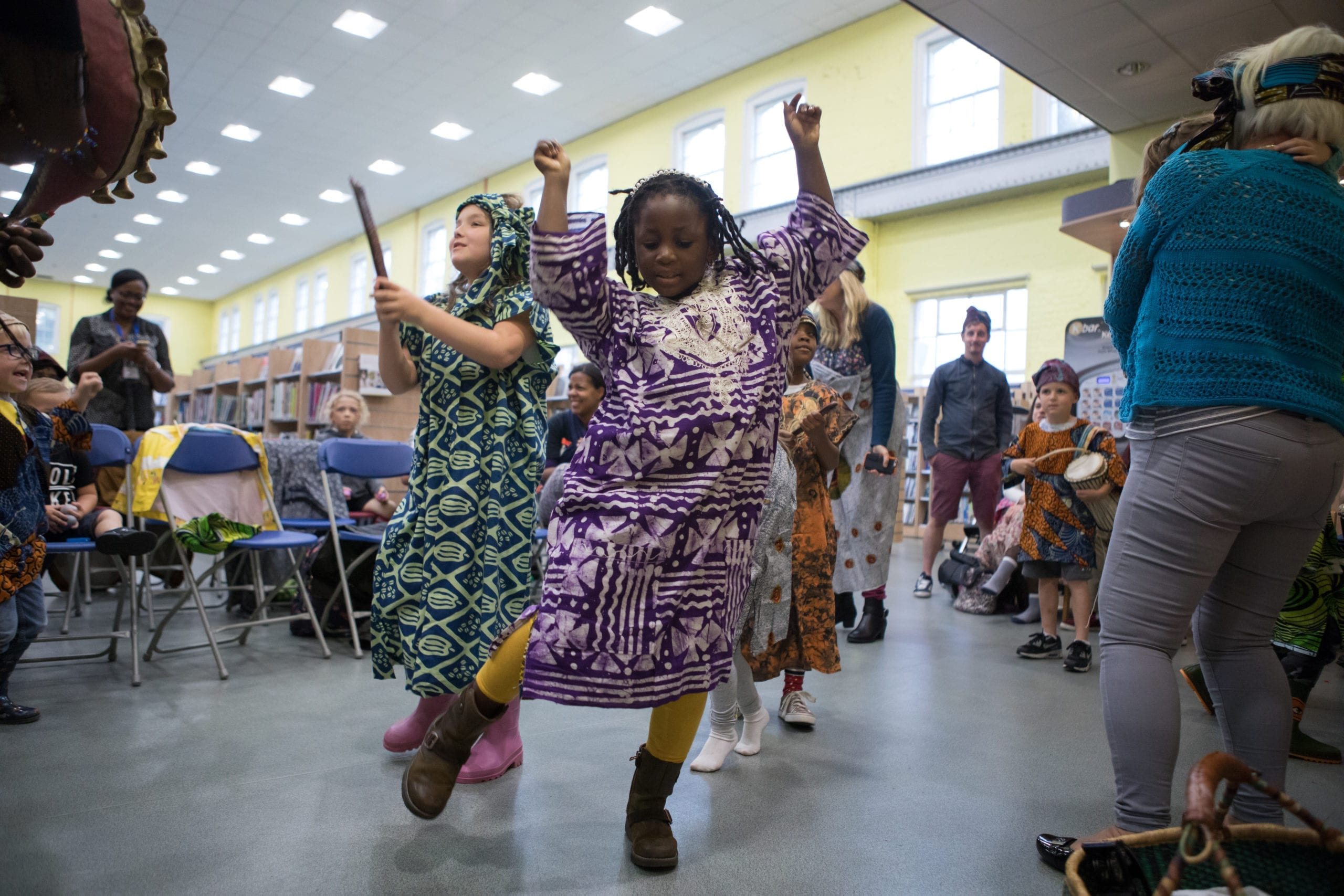 Young children dancing and playing percussion instruments