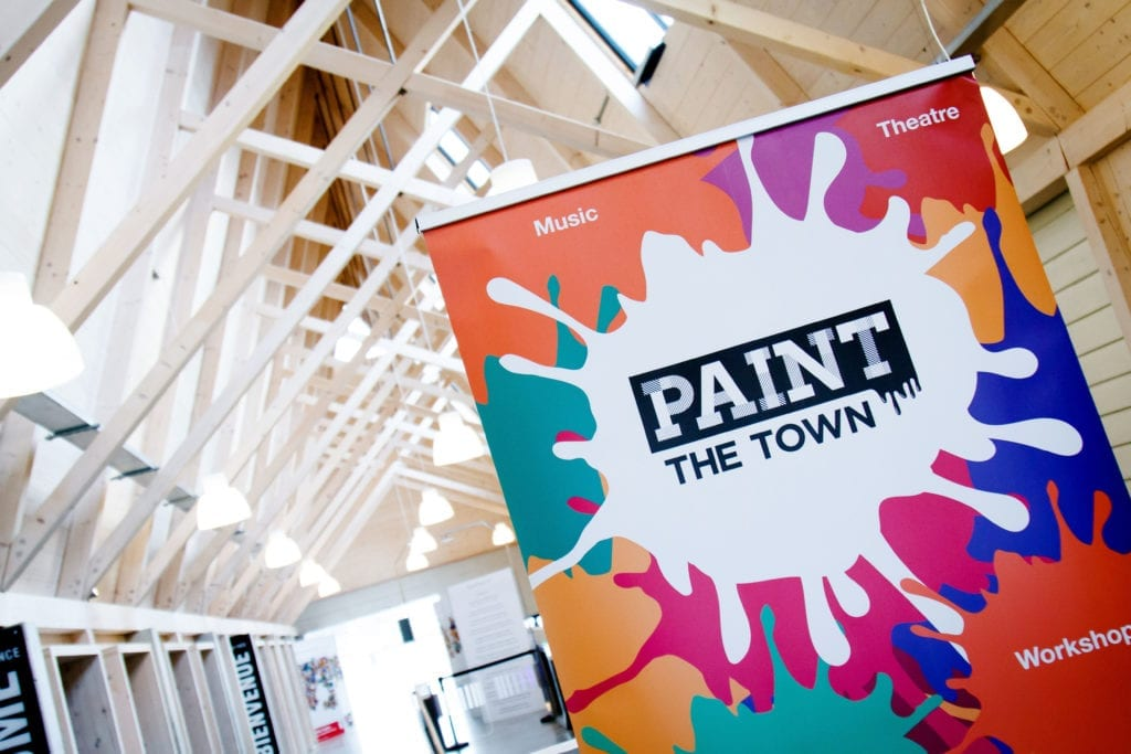 A poster for Paint the Town hanging from the ceiling inside a building
