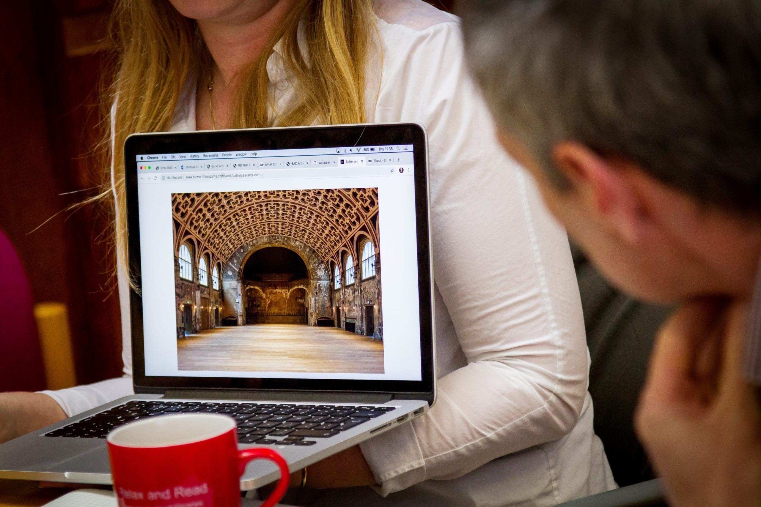 A woman showing people a photo of a building on her laptop
