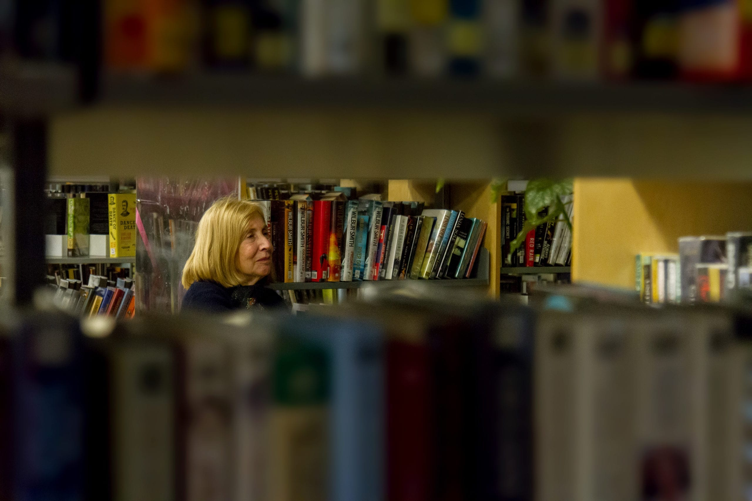 A photo taken of a woman through a shelf of books in a library