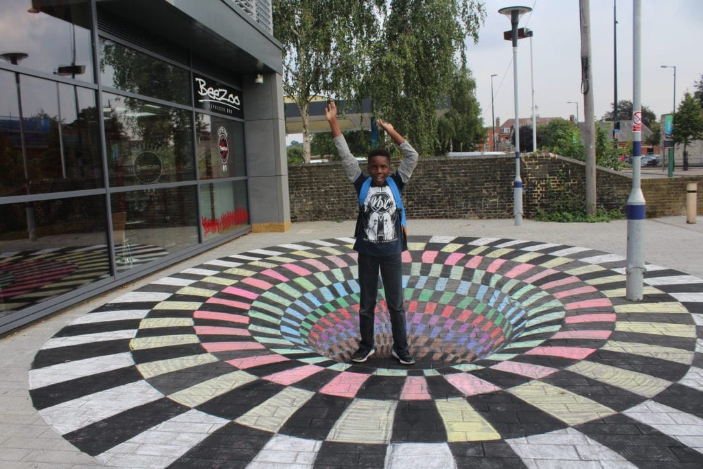 A young boy stood on top of street art of an optical illusion