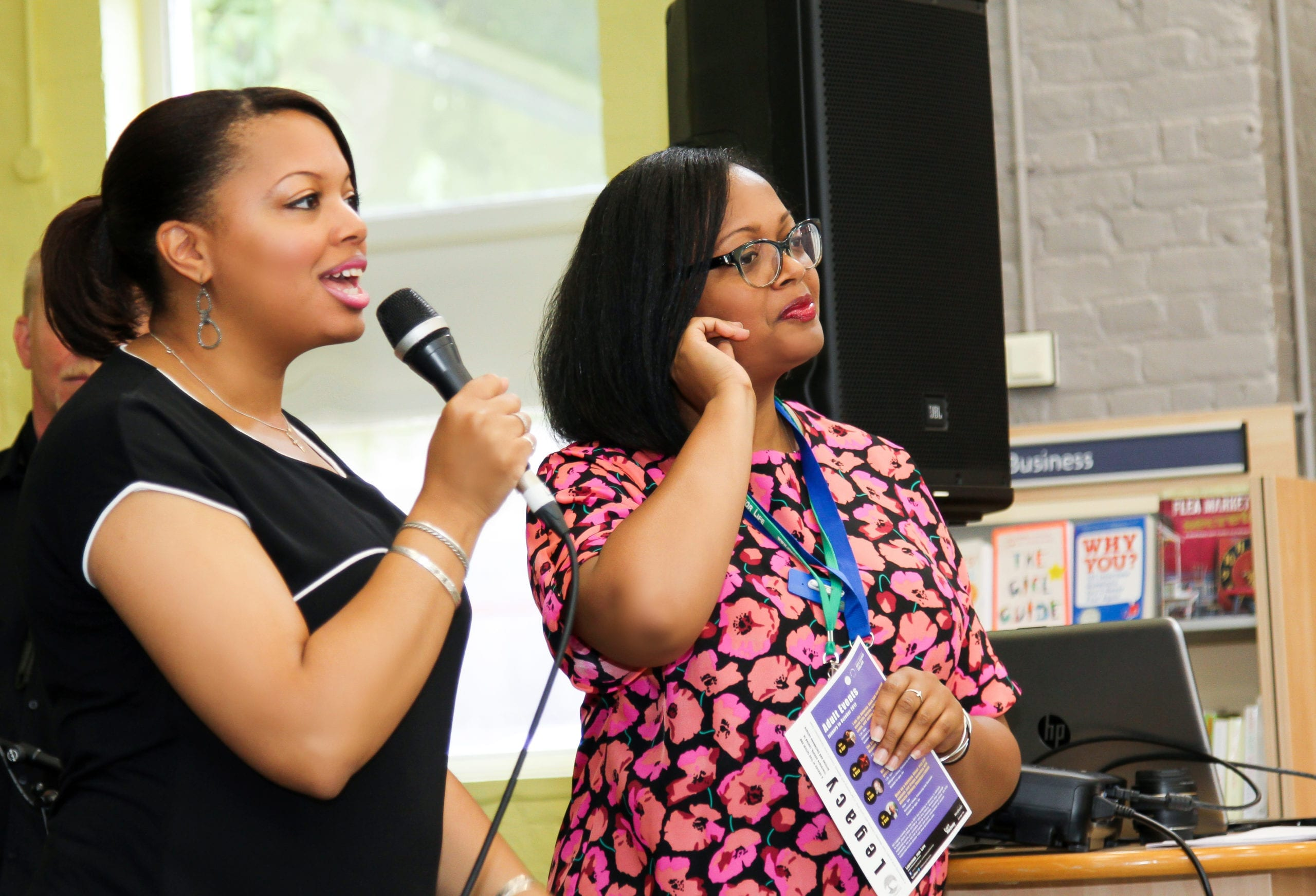 Two Lyrici Arts staff members addressing an audience at an event