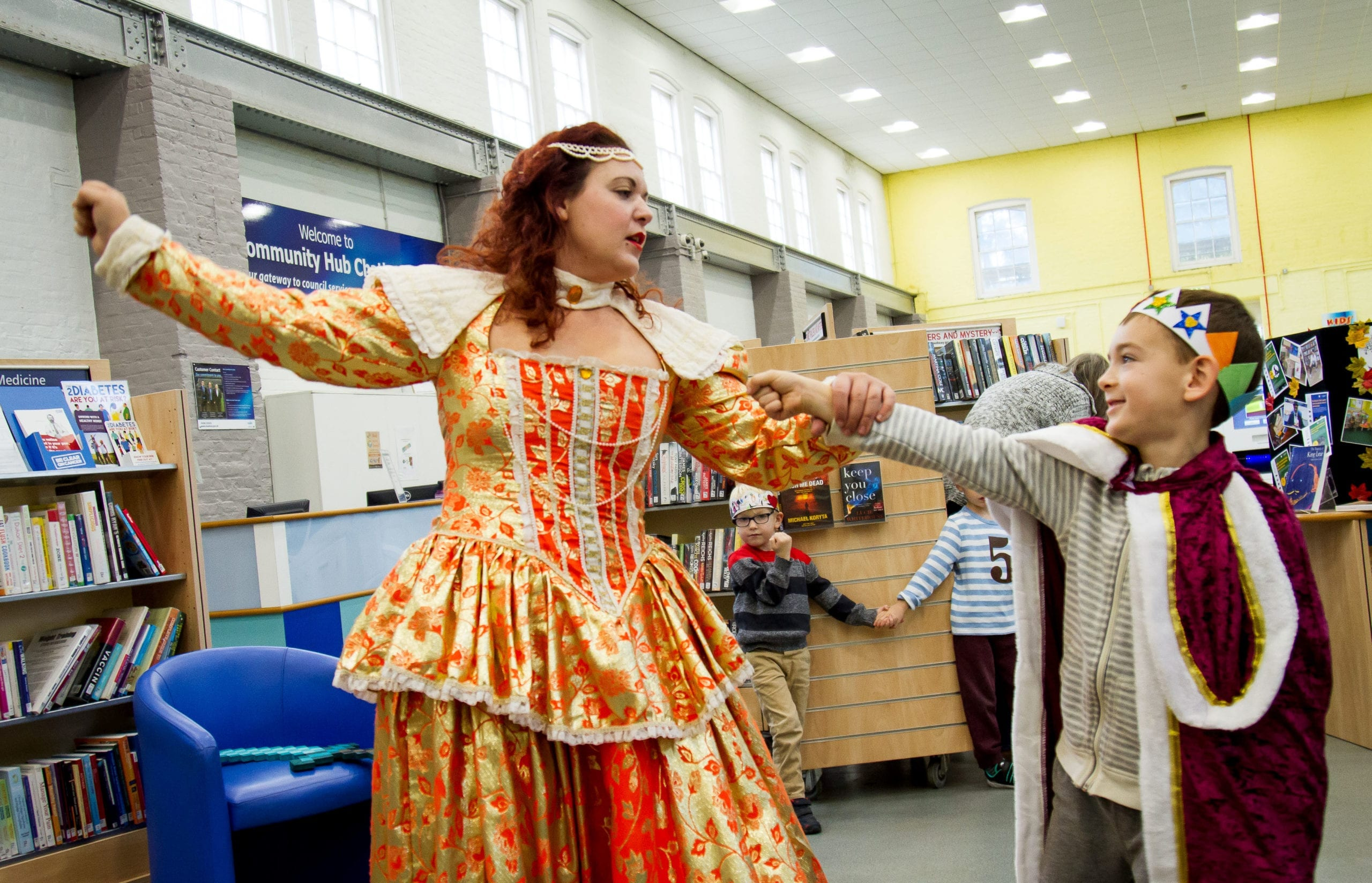 A woman and a young boy dressed up as a king and a queen in a library