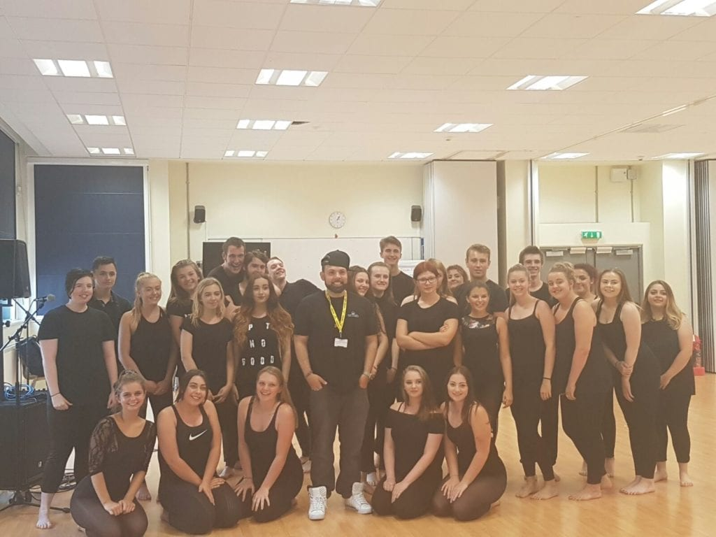 A group photo of performers in a rehearsal space