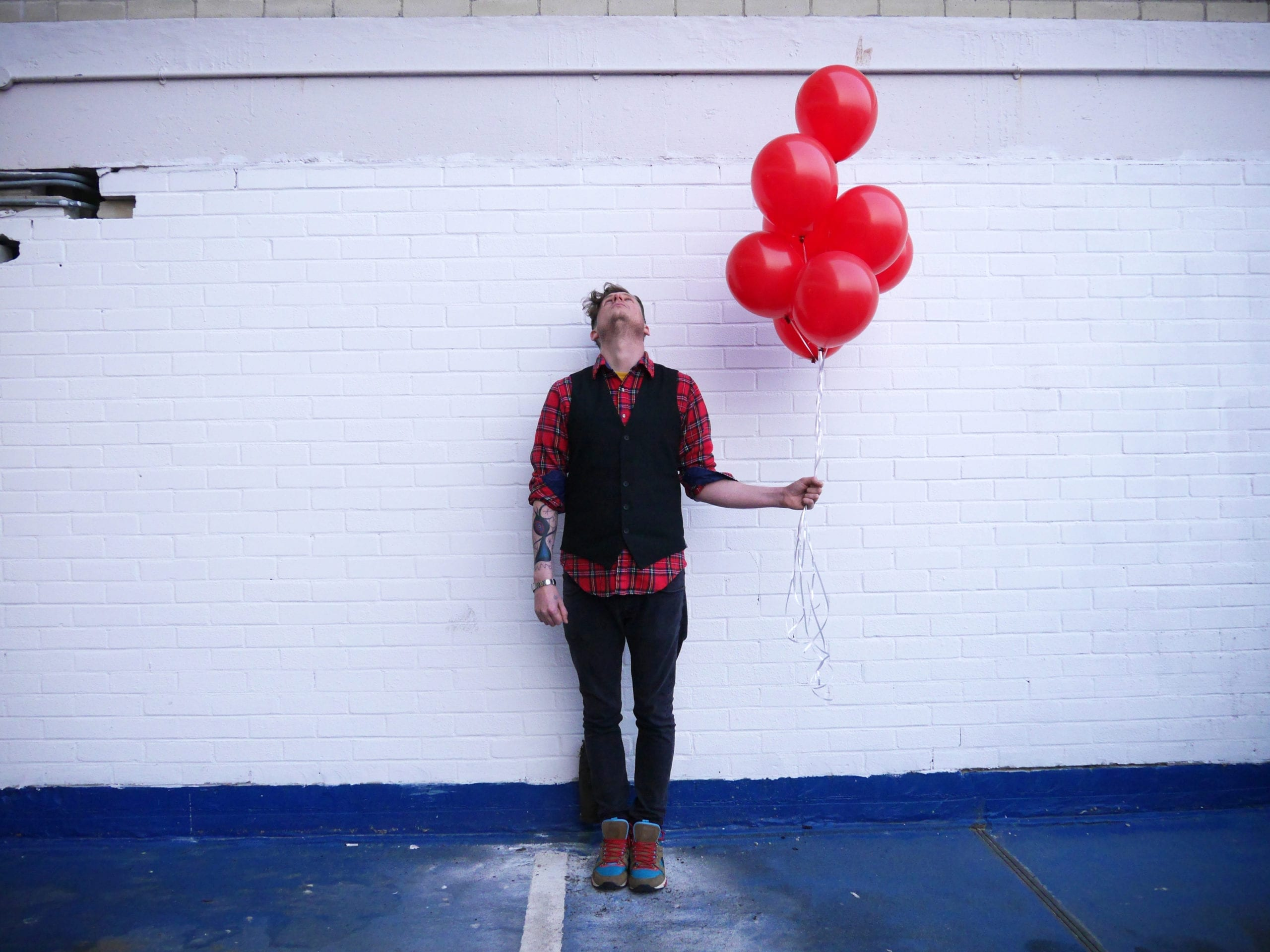 A man holding a bunch of red balloons in front of a white wall