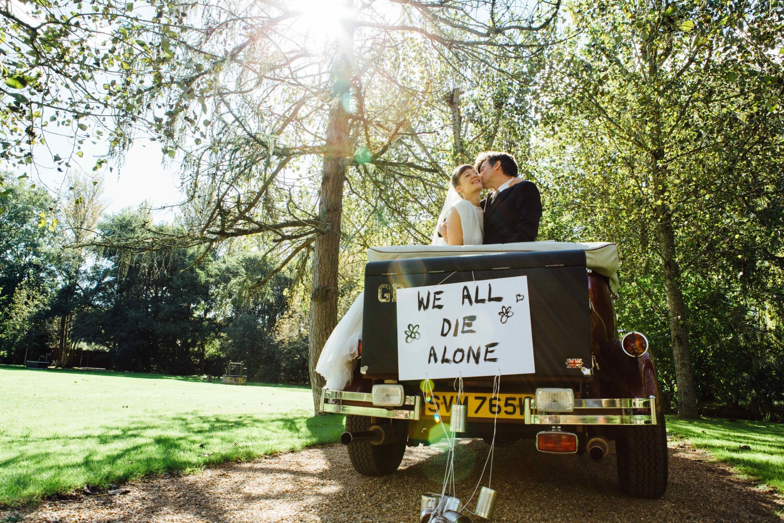A wedding car with a couple kissing and the words 'We all die alone' written on the back