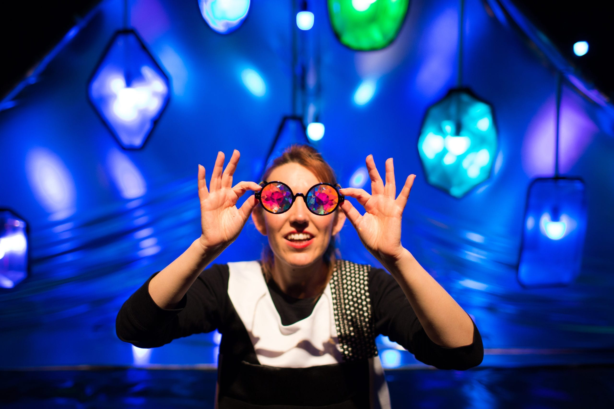 A female actor holding a pair of kaleidoscope glasses up to her eyes