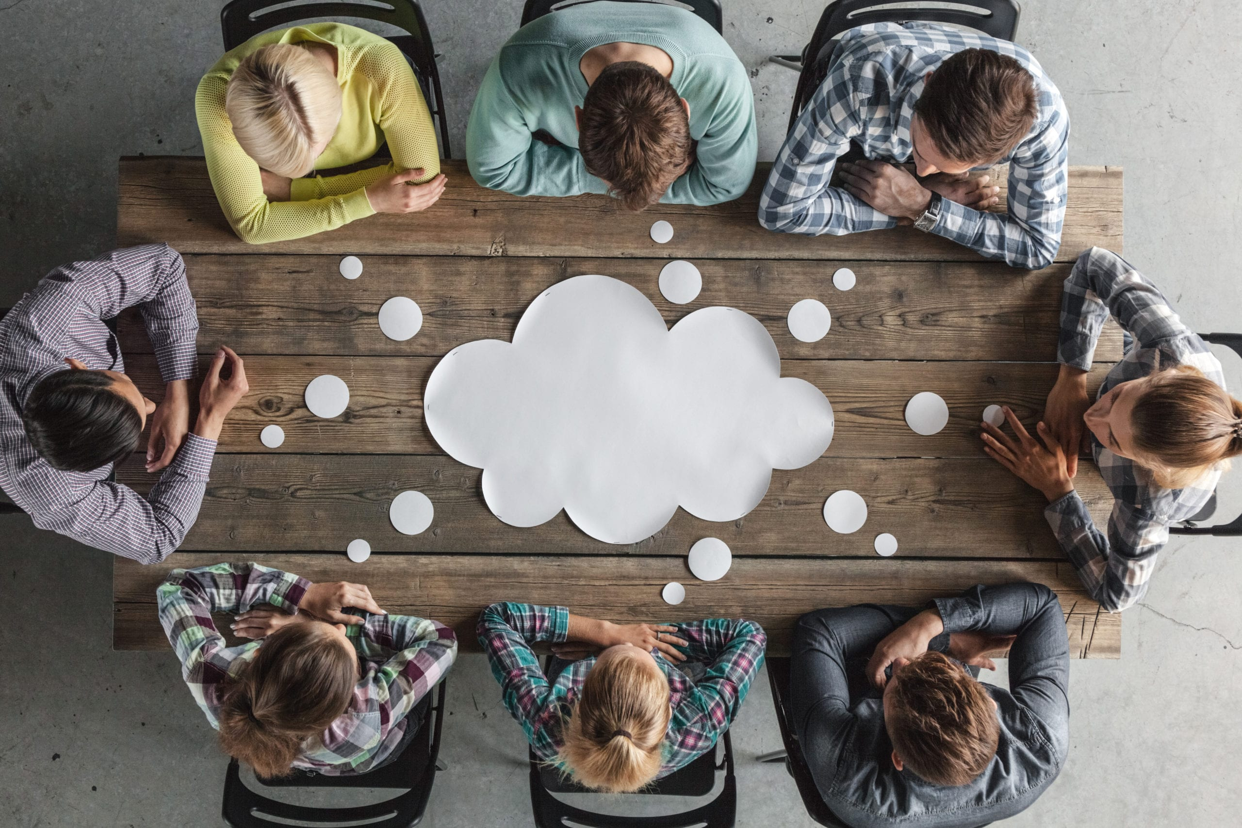 A team of eight seated in a meeting around a table looking at a paper idea bubble.