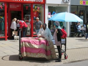Image of a double bed in a high street with one woman under a pink duvet